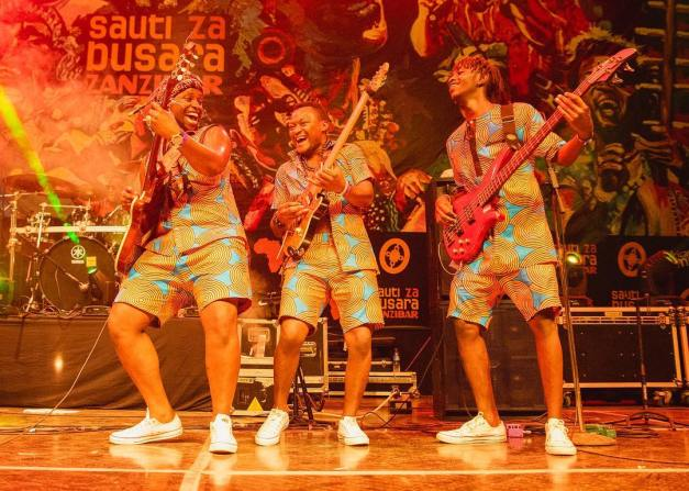Fadhilee and his guitarists smiling on Sauti Za Busara 2019 stage
